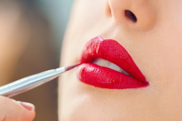 Визажист делает профессиональный макияж молодой женщины