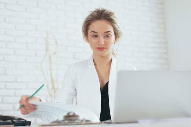 オフィスで働く美しい若い女性の肖像画。