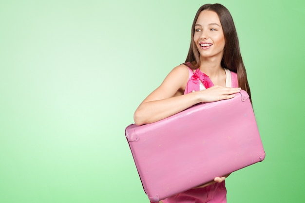 ピンクのスーツケースを持つ女性
