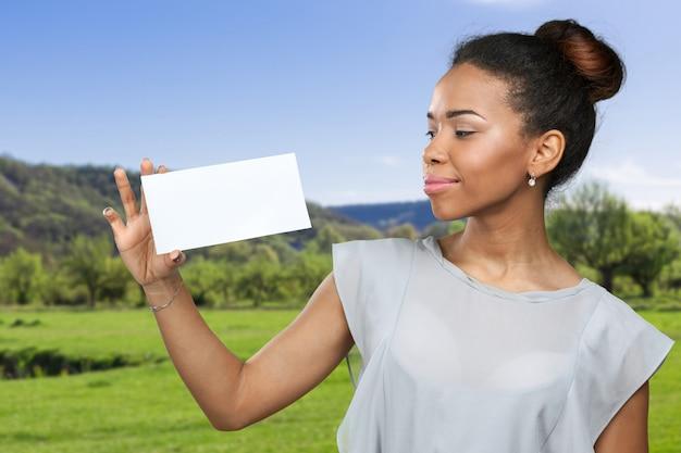 Афро-американских женщина, держащая чистый лист бумаги