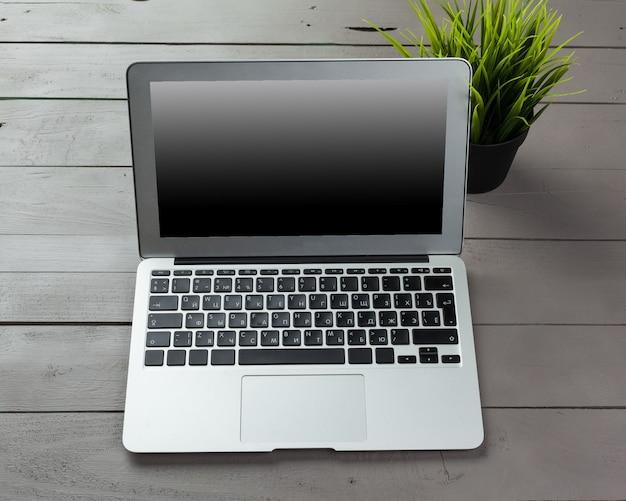 木製の机の上のノートパソコンのキーボード