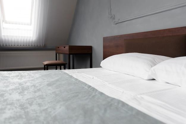 ビューティールームで清潔な白い枕とベッドシーツを備えたベッドメイドアップ。