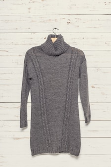 Вязаный свитер на деревянной поверхности вешалка для одежды