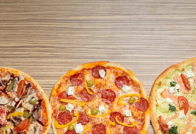 木製の表面テーブルで提供されるおいしいイタリアのピザ