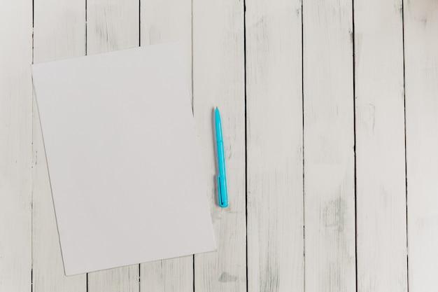 オフィス木製表面テーブルの上にペンで空白のメモ帳