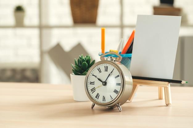 木製のテーブルに目覚まし時計とオフィス文具オブジェクトをクローズアップ