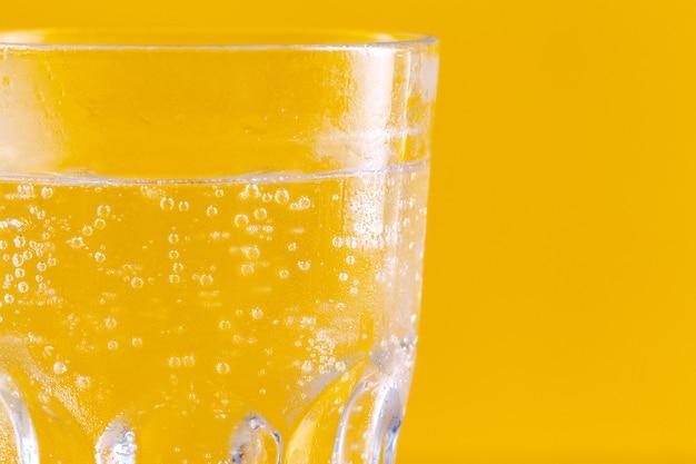 黄色の背景に水の入ったグラス。健康的な生活様式