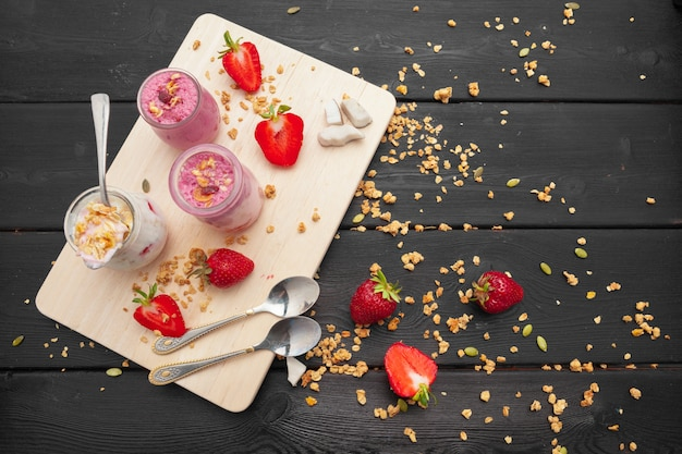 Овсяная каша с йогуртом и ягодами на черном фоне, деревянные. вид сверху. здоровый завтрак.