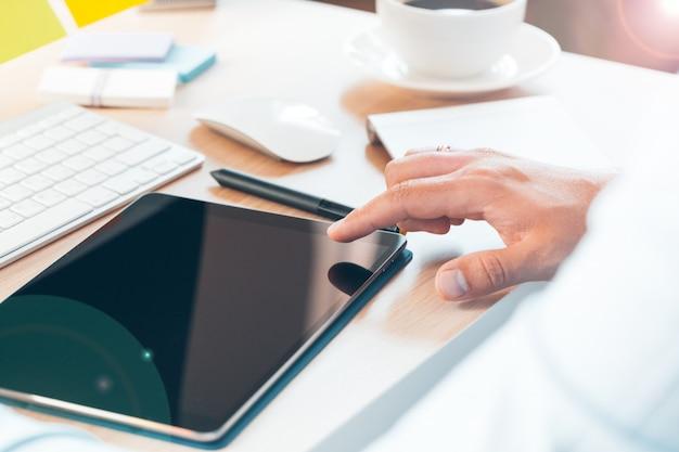 オフィスで現代のデジタルタブレットとコンピューターを使用して男性の手。