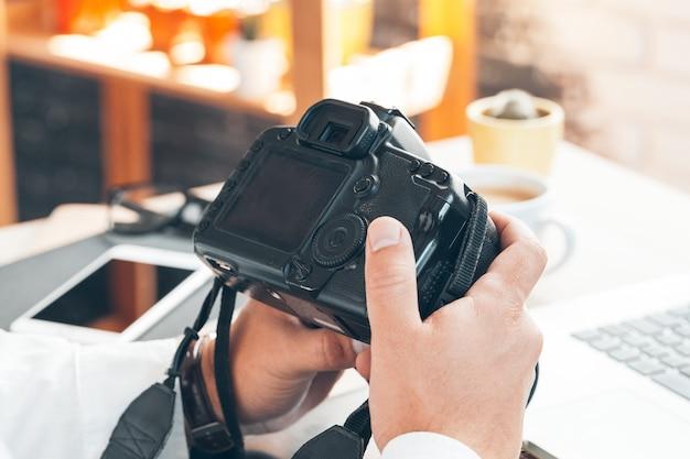 コンピューターに取り組んでいる若い男の写真家。