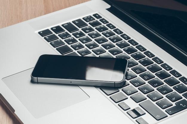 テーブルの上のノートパソコンと携帯電話。
