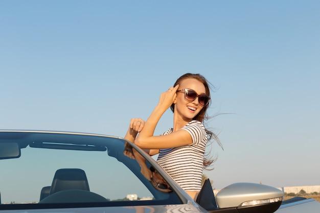 コンバーチブル車の近くの魅力的な若い女性