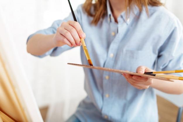 仕事で美しい若い女性画家