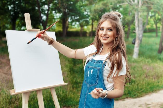 外のキャンバスにペイントする若い白人女性