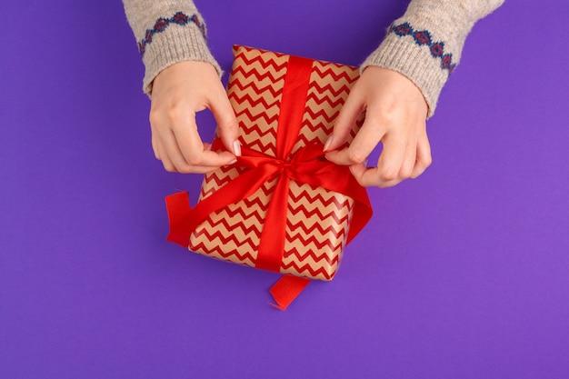 紫に包まれたギフトを保持している女性の手