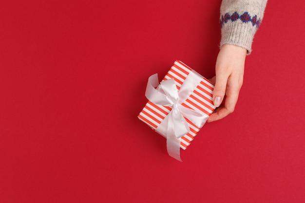赤のクリスマスプレゼントで女性の手