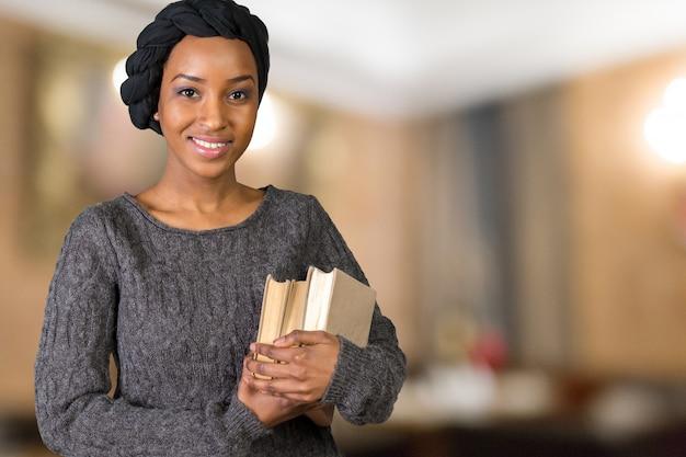 Красивая афро американская женщина держит книги