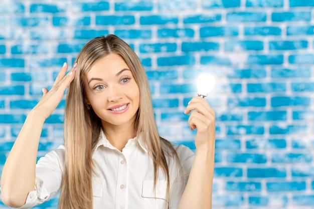 白熱電球のシンボルの横にある若い実業家
