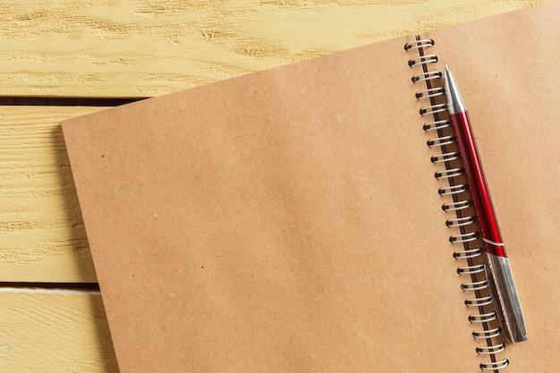 木製の背景にメモ帳を開く