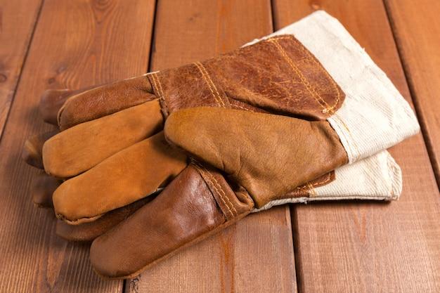 木製の背景に建設用手袋