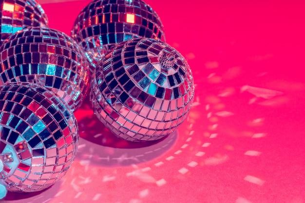 Зеркальные диско шары над розовым. вечеринка, ночная жизнь