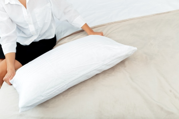 Молодая горничная заправляет кровать в гостиничном номере