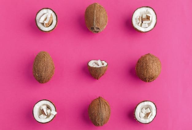 Сломанные кусочки кокоса на ярко-розовом, вид сверху, копия пространства