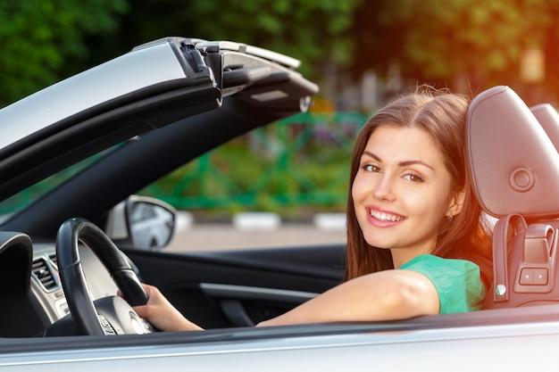 若い女性が街で車を運転します。