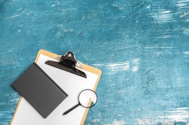 虫眼鏡と木製のテーブルの上のノート