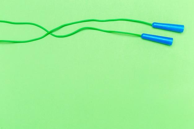 Зеленая резиновая скакалка с голубыми ручками сверху