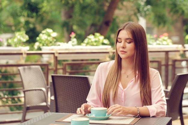 屋外のカフェでコーヒーを飲む若い女性