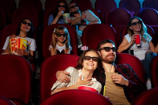 Друзья сидят в кино, смотрят фильм, едят попкорн и пьют воду.