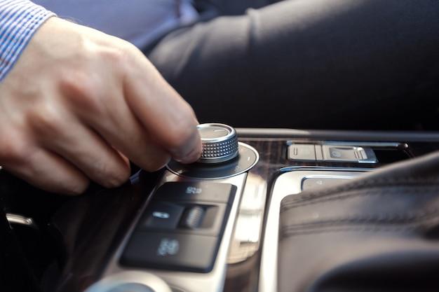 電源ボタンを押してカーステレオシステムをオンにする手