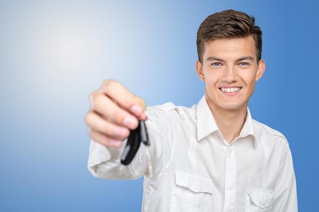 車のキーを保持している若い笑みを浮かべて男