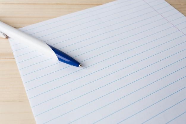 Крупный план шариковой ручки на линованной бумаге