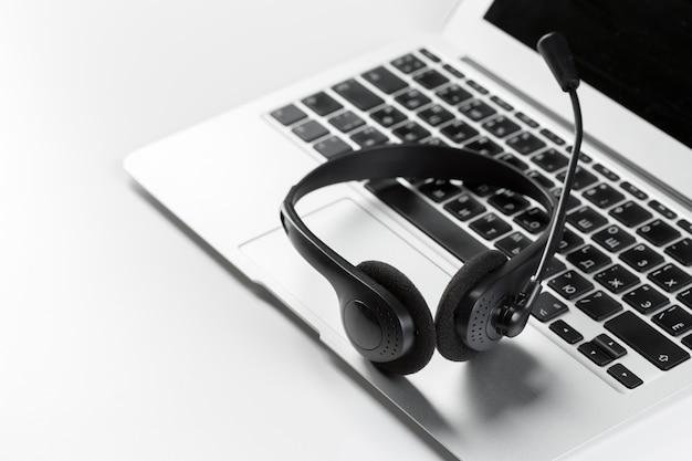 コールセンターサポート。キーボードコンピューターのラップトップ上のヘッドセット