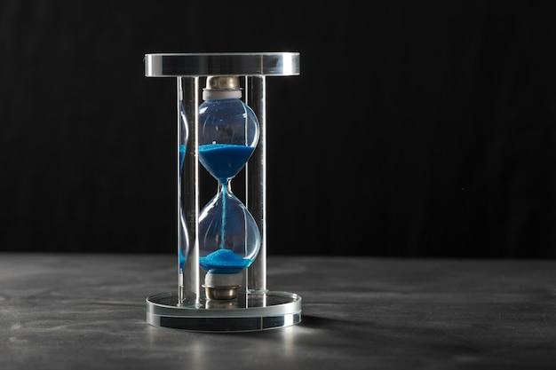時間は過ぎています。青い砂時計をクローズアップ
