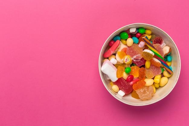 ピンクの背景にカラフルなキャンディー