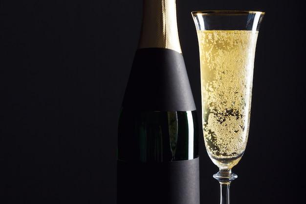 Бокал шампанского и бутылка на черном