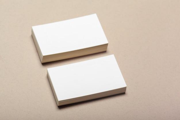 ベージュ色の背景にモックアップのための空白の紙片