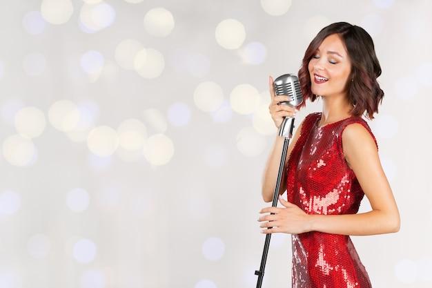 分離された赤い光沢のあるドレスの女性歌手