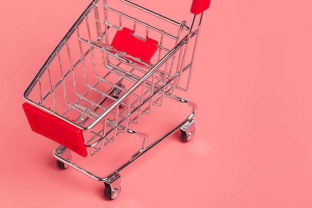 Корзина или тележка для супермаркета на розовом