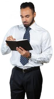 白で隔離される彼のメモ帳を保持している黒人男性ビジネスマン