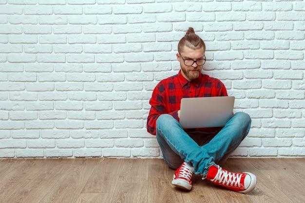 ラップトップで床に座っている若い男