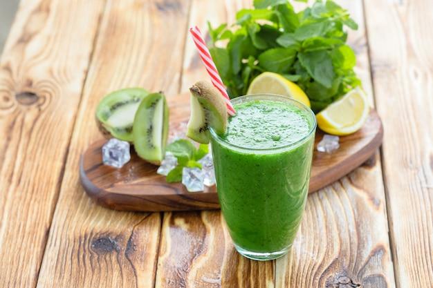 木製テーブルの上の果物と野菜の緑のスムージー