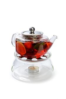 Стеклянный заварной чайник с кусочками фруктов на белом фоне