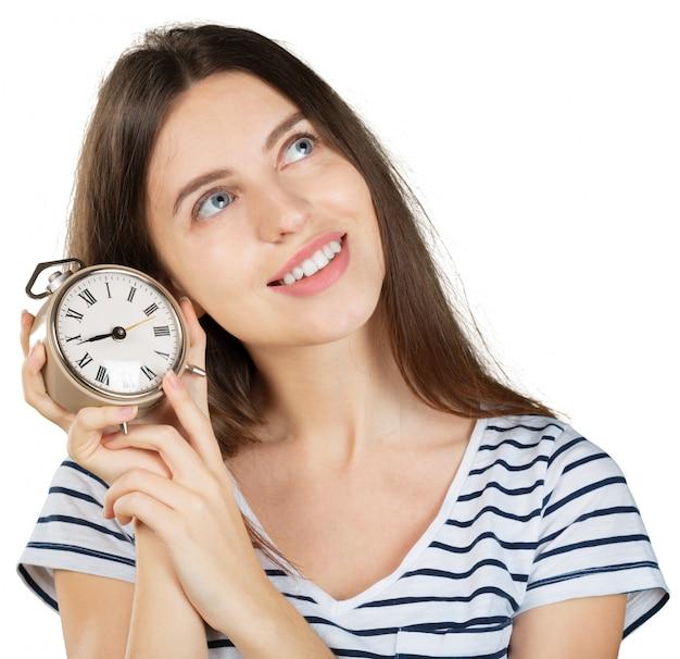 白で隔離の目覚まし時計を持つ若い女性。時間管理の概念