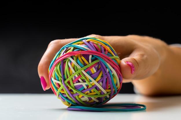 カラフルな輪ゴムのボールを持つ女性の手