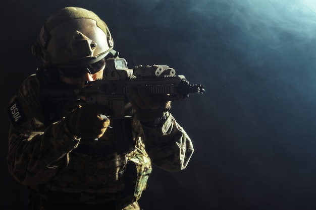 暗い背景にライフルを持つ特殊部隊の兵士
