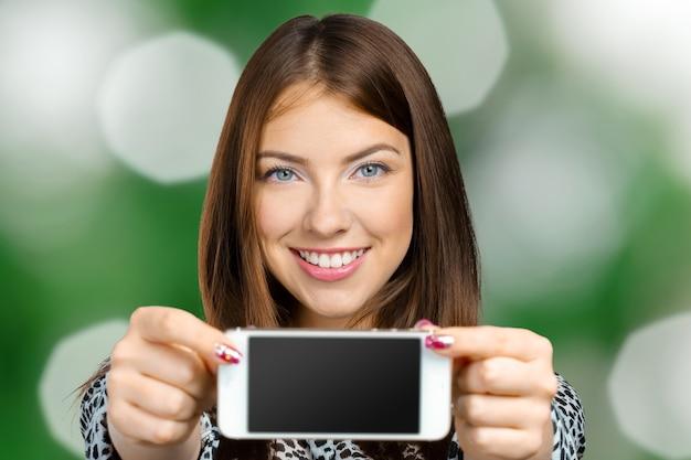 Улыбается женщина, показывая экран смартфона
